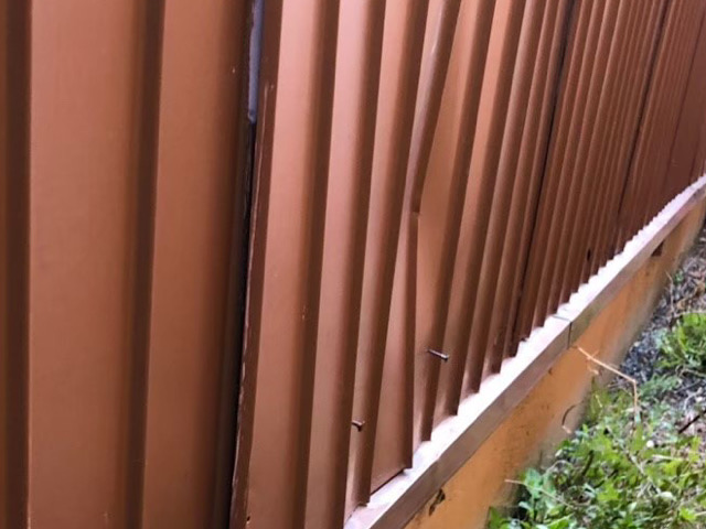 凹んでいるトタンの壁